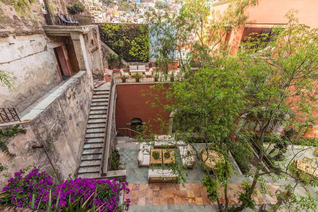 the internal patio of a luxury hotel  with bugainvilleas and stairs - Where to stay in Guanajuato