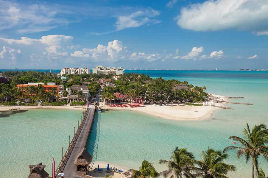 a bridge over turquoise water - things to do in Isla Mujeres