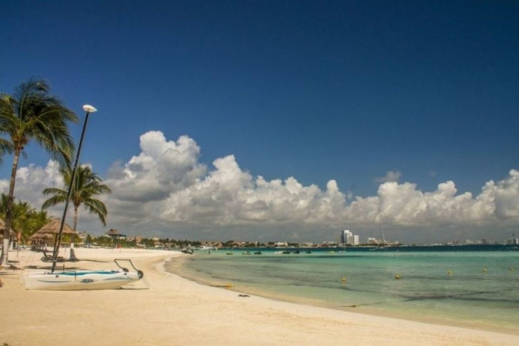 Cancun beach with clouds in the sky and a kayak on the beach