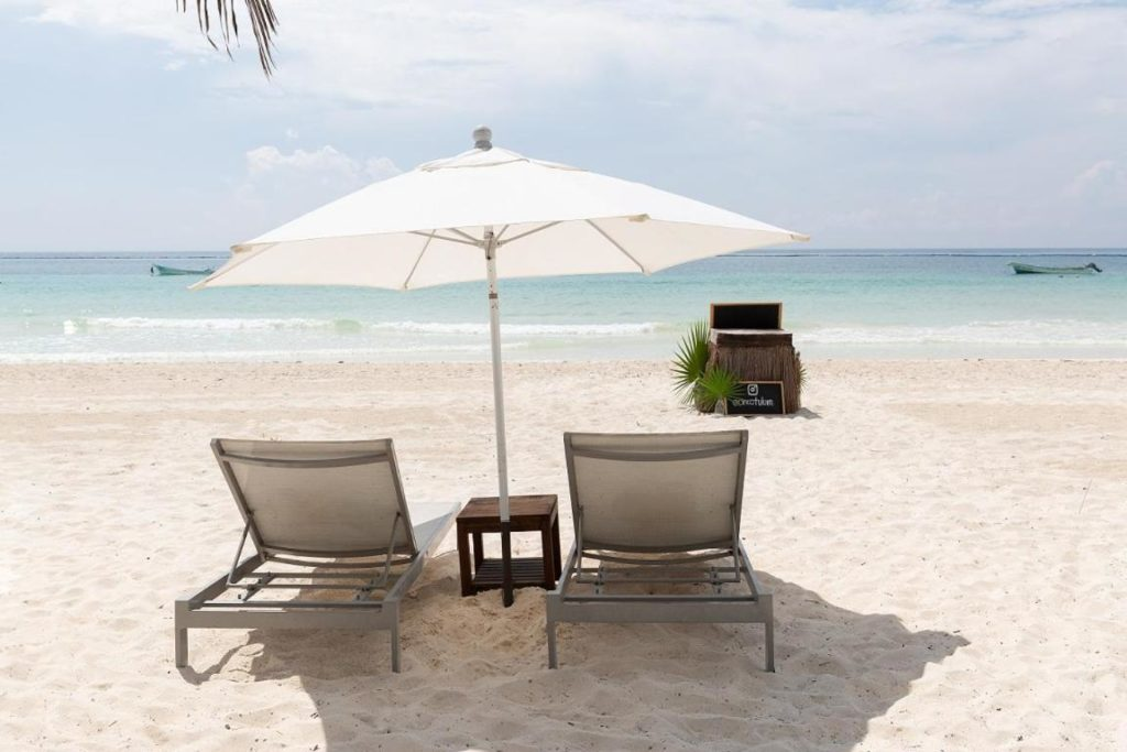 tulum beach with chairs and umbrella