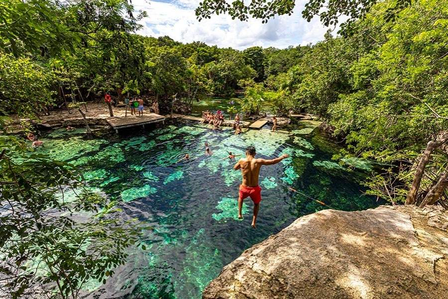 boy jumping from the trampoline to the cenote
